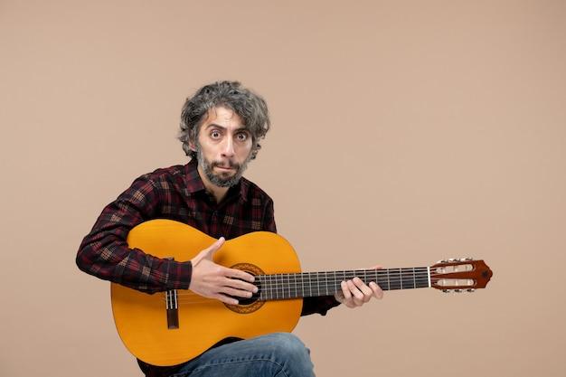 분홍색 벽에 기타를 든 젊은 남성의 전면 모습