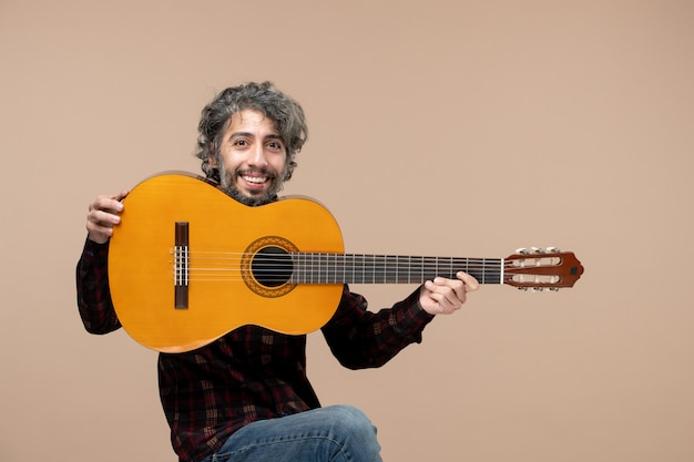 ピンクの壁にギターと若い男性の正面図