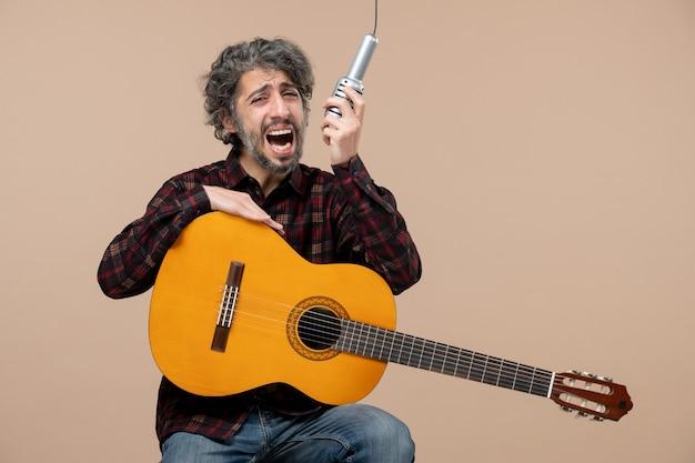 분홍색 벽에 마이크에 기타 노래와 함께 젊은 남성의 전면 보기