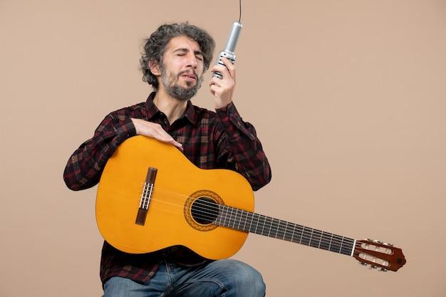 ピンクの壁のマイクでギターを歌っている若い男性の正面図