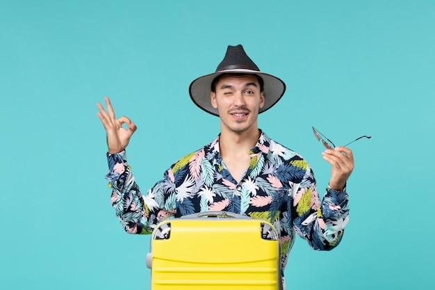 青い壁に長い旅行の準備をしている彼の黄色いバッグを持つ若い男性の正面図