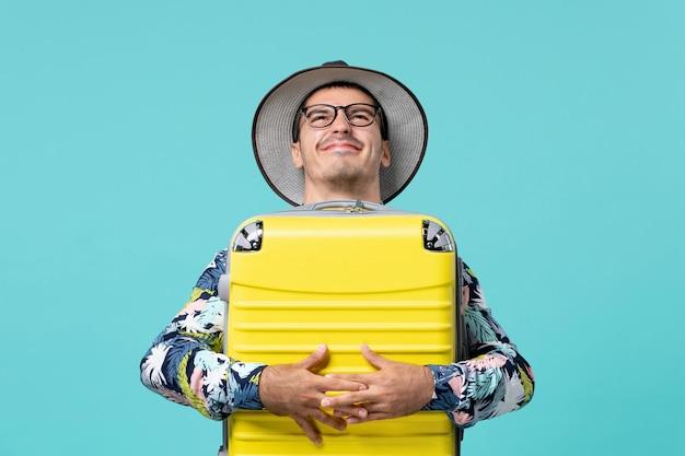 파란색 벽에 여행을 준비하는 그의 노란색 가방을 가진 젊은 남성의 전면보기
