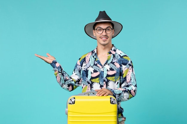 青い壁に旅行の準備をしている彼の黄色いバッグを持つ若い男性の正面図
