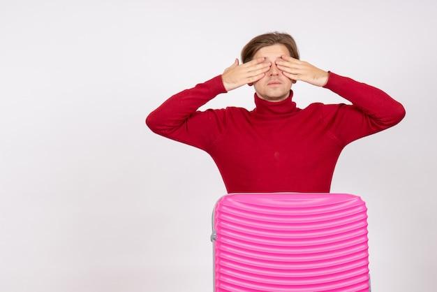 Вид спереди молодого мужчины с розовой сумкой и закрытыми глазами на белой стене