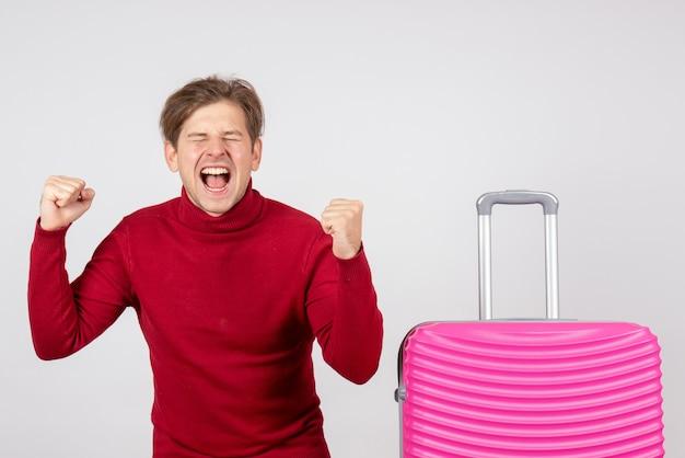 Вид спереди молодого мужчины с розовой сумкой, эмоционально радуясь на белой стене