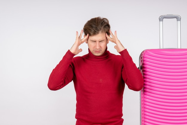 Вид спереди молодого мужчины с розовой сумкой с головной болью на белой стене