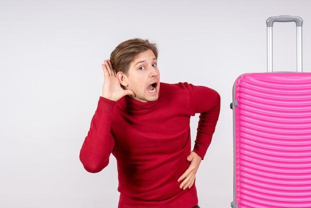 白い壁にピンクのバッグを持つ若い男性の正面図