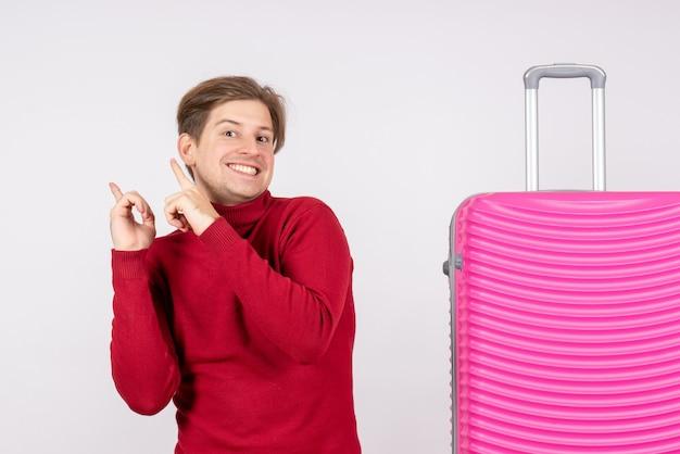 Вид спереди молодого мужчины с розовой сумкой на белой стене