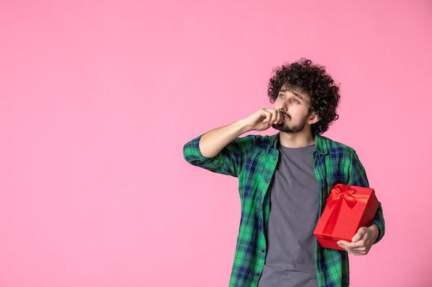 Вид спереди молодого мужчины с красным пакетом на светло-розовой стене