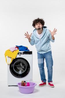 흰 벽에 세탁기와 더러운 옷을 입은 젊은 남성의 전면