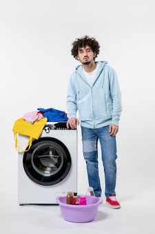 白い壁に洗濯機と汚れた服を着た若い男性の正面図