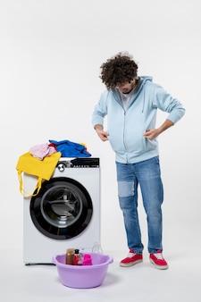Вид спереди молодого мужчины с стиральной машиной и грязной одеждой на белой стене