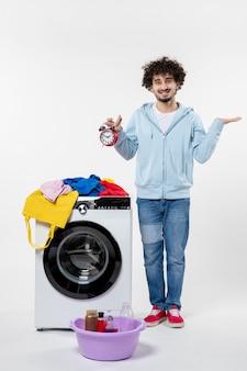 白い壁に時計を保持している洗濯機を持つ若い男性の正面図