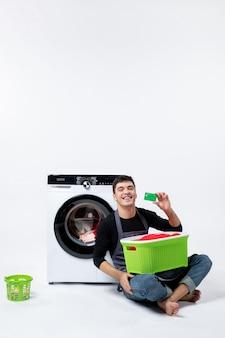 白い壁に緑の銀行カードを保持している洗濯機を持つ若い男性の正面図