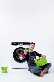 軽い壁に緑の銀行カードを保持している洗濯機を持つ若い男性の正面図