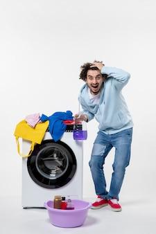 白い壁に液体粉末を保持している洗濯機を持つ若い男性の正面図