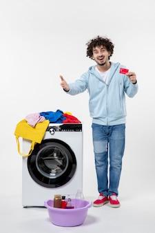 赤い銀行カードを保持し、白い壁に誰かに挨拶する洗濯機を持つ若い男性の正面図