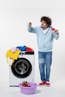 白い壁に赤い銀行カードを保持している洗濯機を持つ若い男性の正面図