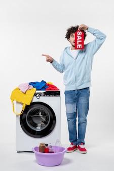흰색 벽에 빨간색 판매 배너를 들고 세탁기와 젊은 남성의 전면 보기