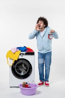 흰 벽에 빨래가 끝날 때까지 세탁기가 있는 젊은 남성의 전면