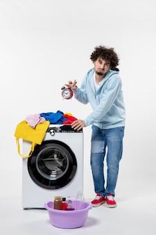 Вид спереди молодого мужчины со стиральной машиной, ожидающего окончания стирки одежды на белой стене