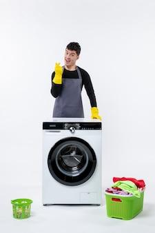 Вид спереди молодого мужчины со стиральной машиной и грязной одеждой на белой стене