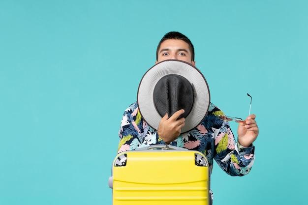 帽子を保持し、水色の壁で旅行の準備をしている黄色のバッグを持つ若い男性の正面図