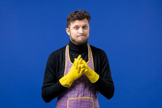 青い壁に立っている黄色の排水手袋を持つ若い男性の正面図