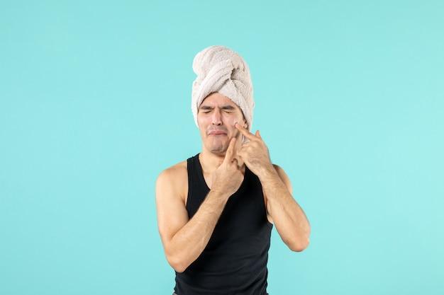 青い壁に小さなにきびを絞り出そうとしているシャワーの後の若い男の正面図