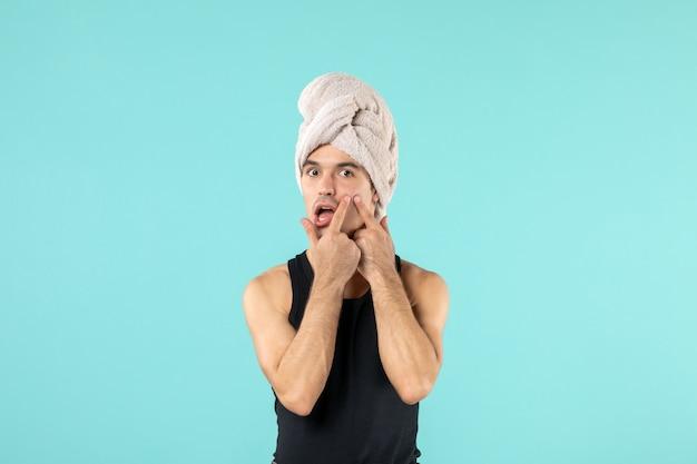 파란색 벽에 머리에 수건을 얹은 샤워 후 젊은 남자의 전면