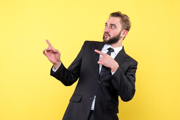 若い男の正面図驚くべきビジネスマン黄色に指を脇に向ける