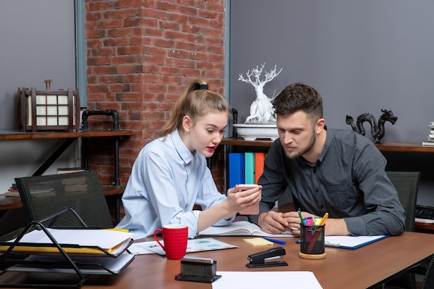 사무실 환경에서 한 가지 문제를 논의하는 테이블에 앉아 있는 젊은 남자와 그의 여성 동료의 전면 모습