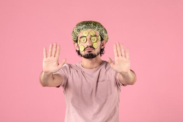 분홍색 벽에 얼굴에 오이 마스크를 적용하는 젊은 남자의 전면 보기