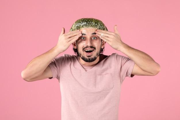 분홍색 벽에 얼굴에 마스크를 바르는 젊은 남자의 전면