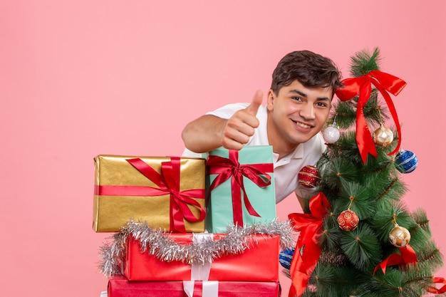 ピンクの壁にクリスマスプレゼントと休日の木の周りの若い男の正面図