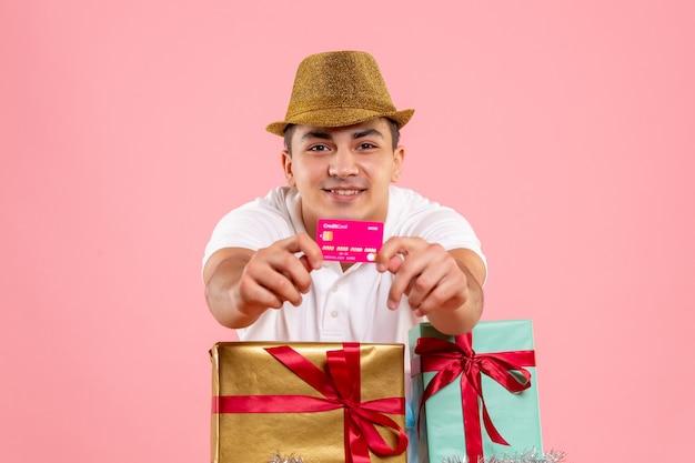 Вид спереди молодого человека вокруг рождественских подарков держит банковскую карту на розовой стене