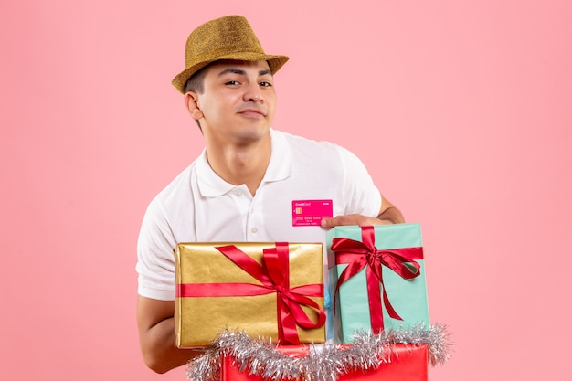 크리스마스 주위에 젊은 남자의 전면보기 분홍색 벽에 은행 카드를 들고 선물