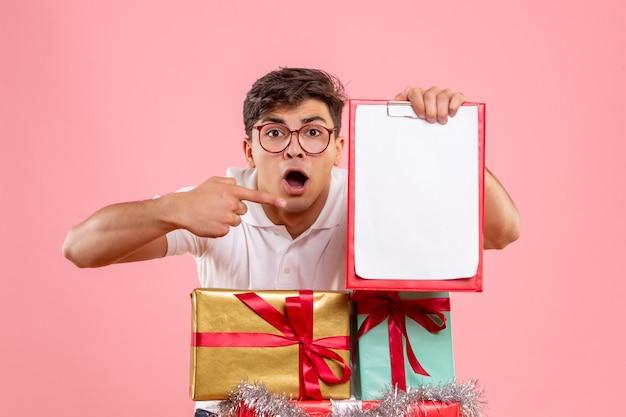 クリスマスの周りの若い男の正面図はピンクの壁にファイルノートを保持している