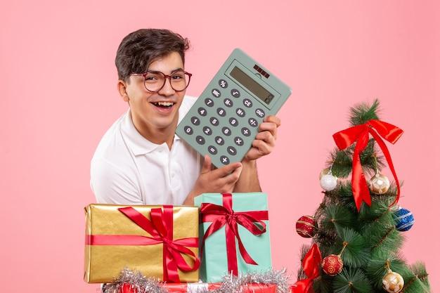 Вид спереди молодого человека вокруг рождественских подарков с калькулятором на розовой стене