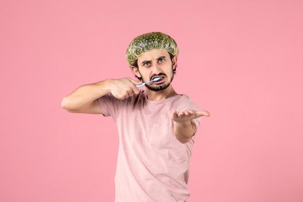 Вид спереди молодого человека, чистящего зубы на розовой стене