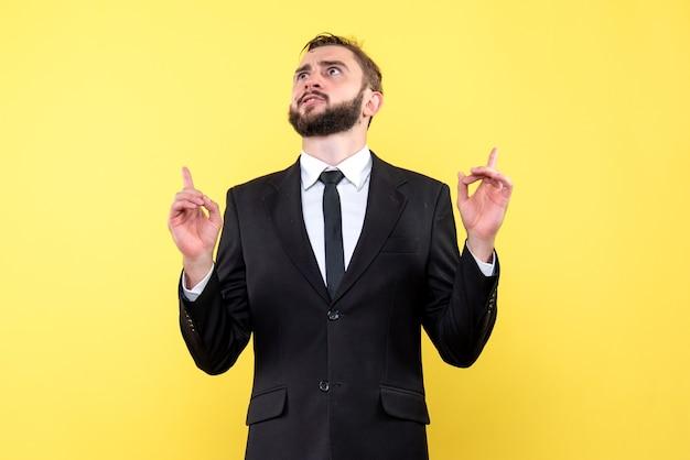 黄色の上に指を指している疑いを持つ若い男のビジネスマの正面図