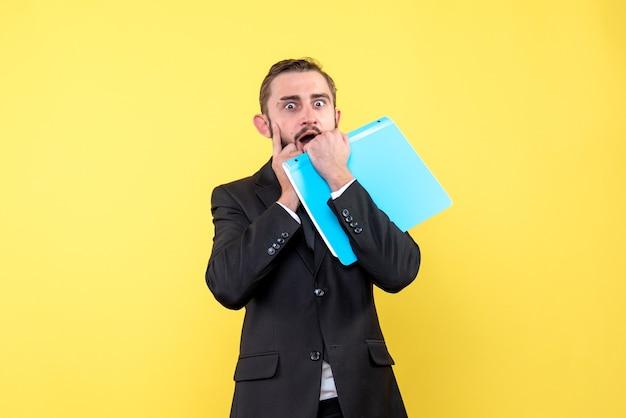 人差し指を頬に押し付け、黄色の青いフォルダーを保持している新しいアイデアを持っている若い男のビジネスマンの正面図
