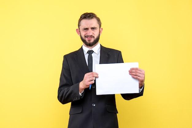Вид спереди молодого человека-бизнесмена в костюме сбит с толку, он строго задает вопросы на желтом