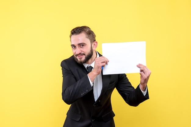 미소 한 벌에 젊은 남자 사업가의 전면보기 노란색에 왼쪽에 빈 종이를 옆으로 유지