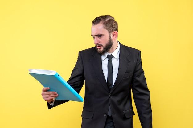 若い男のビジネスマンの正面図は、黄色の青いフォルダーをチェックしながら怒っているように見えます