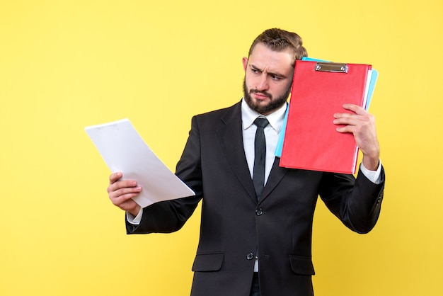 Вид спереди бизнесмена молодого человека касается его головы папками и серьезно рассматривает документ на желтом