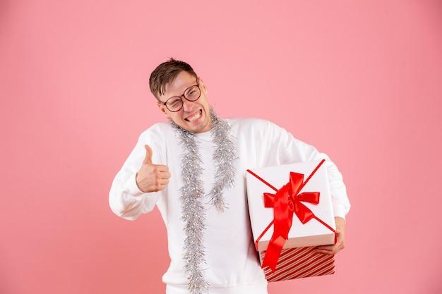 ピンクの壁にクリスマスプレゼントを運ぶ若い男の正面図