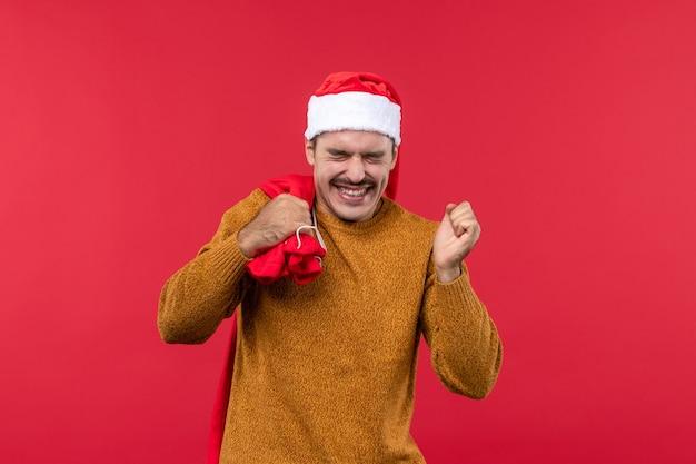 明るい赤の壁にプレゼントバッグを運ぶ若い男の正面図