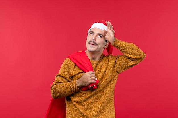 赤い壁に赤いプレゼントバッグを運ぶ若い男の正面図