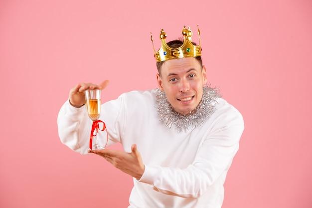 ピンクの壁に飲み物とクリスマスを祝う若い男の正面図